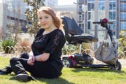 Woman-sitting-on-the-grass-at-city-park-with-her-mobility-scooter