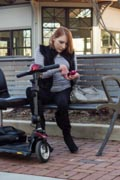Woman-sitting-on-park-bench-texting-with-her-mobility-scooter