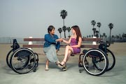Two-women-in-wheelchairs-at-beachside-park