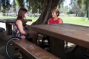 Two-women-using-wheelchairs-at-picnic-table-in-park