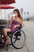 Woman-using-wheelchair-having-coffee-at-the-beach
