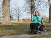 Young-woman-using-wheelchair-in-suburban-park-in-Winter
