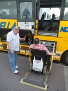 Wheelchair-used-and-helper-using-lift-to-get-onto-coach