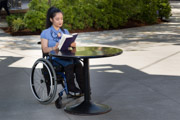 A-young-woman-using-wheelchair-reading-book-at-sidewalk-cafe
