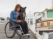 Woman-using-wheelchair-with-her-dog-on-an-outing-at-coastal-marina