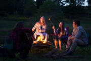 Young-woman-using-wheelchair-sitting-around-firepit-with-her-friends