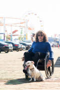 Man-using-wheelchair-on-the-Santa-Monica-Pier-with-his-dog