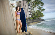 Young-woman-sufer-with-her-board-observing-the-ocean