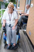 Disabled-couple-leaving-their-house-down-concrete-wheelchair-ramp,