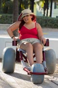 Young-woman-enjoying-the-ocean-in-beach-wheelchair