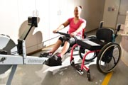 Young-woman-using-rowing-machine-in-rehabilitation-gym