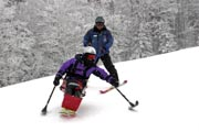 Woman-learning-to-sit-ski-at-an-alpine-ski-field