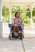 Woman-using-power-wheelchair-in-park-with-her-family