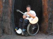 Man-in-wheelchair-playing-guitar-in-giant-redwood