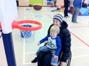 Mother-in-wheelchair-playing-basketball-with-her-young-child