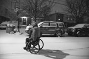 Man-in-wheelchair-out-in-snow-storm-in-suburban-street