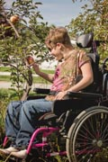 Young-woman-in-wheelchair-picking-apples