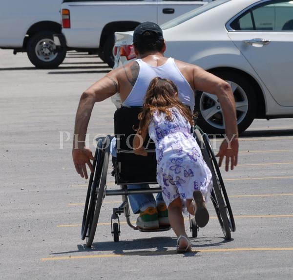 Man in a wheelchair being pushed by his young daughter