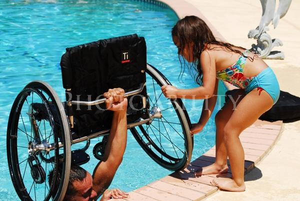Man handing his daughter his wheelchair from the swimming pool