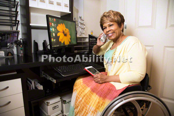 Woman using a wheelchair on the phone in front of her computer