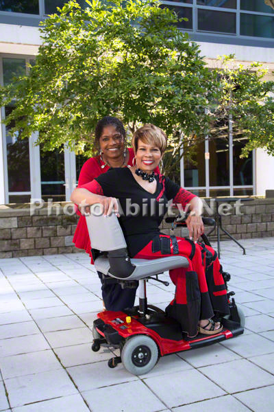 Woman using a wheelchair and her friend outside their office building