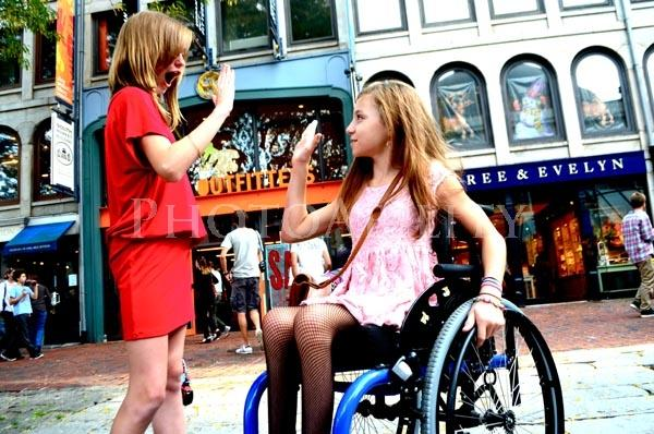 Young woman in a wheelchair in the city with her friend