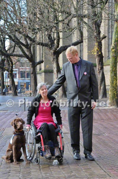Couple on a city sidewalk with their service dog