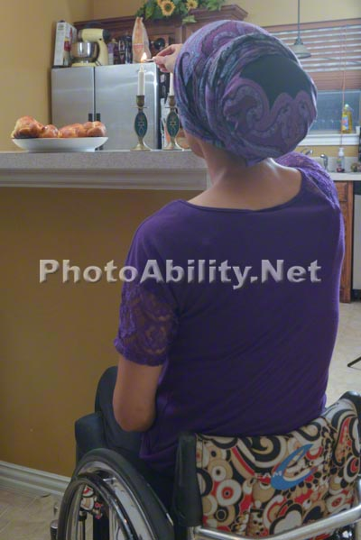Young mother to be in a wheelchair preparing dinner with her family