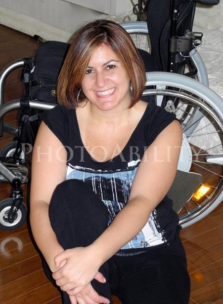 Young woman sitting on the floor next to her wheelchair