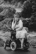 Young-woman-in-power-wheelchair-enjoying-her-home-garden