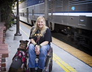 Young-woman-in-wheelchair-on-train-station-with-her-service-dog