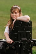 Young-woman-in-power-wheelchair-enjoying-her-home-garden