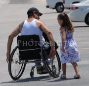 Man-in-wheelchair-talking-to-his-young-daughter