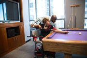 Woman-using-mobility-scooter-playing-game-of-pool-with-her-co-office-workers
