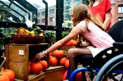 Young-girl-in-wheelchair-shopping-for-pumpkins-with-her-family