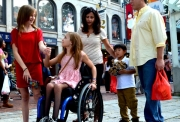 Young-girl-in-wheelchair-in-city-street-shopping-with-her-family
