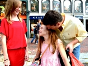 Young-girl-in-wheelchair-in-city-street-with-her-father-and-friend-