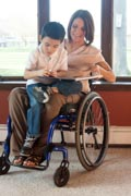 Young-mother-in-wheelchair-reading-story-book-to-her-son