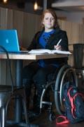 Young-woman-using-wheelchair-studing-on-her-laptop-in-cafe