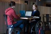 Young-woman-using-wheelchair-studying-in-cafe-with-her-friend