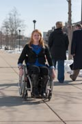 Young-woman-using-wheelchair-on-city-sidewalk-in-winter