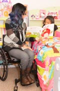 Young-mother-in-wheelchair-reading-bedtime-story-to-her-daughter