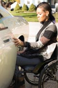 Young-woman-in-wheelchair-getting-into-her-car