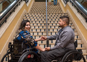 Young-couple-in-wheelchairs-in-front-of-shopping-mall-staircase