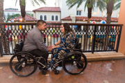 Young-couple-in-wheelchairs-embracing-on-city-balcony
