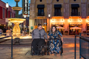Young-couple-in-wheelchairs-on-romantic-night-out-in-city-square