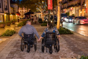 Young-couple-in-wheelchairs-holding-hands-on-romantic-night-out