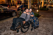 Young-couple-in-wheelchairs-embracing-on-city-sidewalk