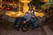 Young-couple-in-wheelchairs-embracing-in-front-of-fountain