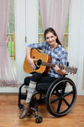 Young-woman-using-wheelchair-listening-to-and-playing-music